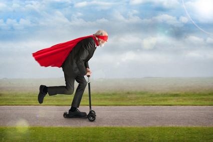 senior superhero man riding a scooter Elektroroller Kaufen